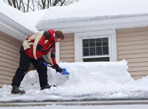Man shoveling snow off roof