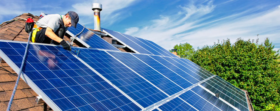 Contractor installing solar panels on eco-friendly roof