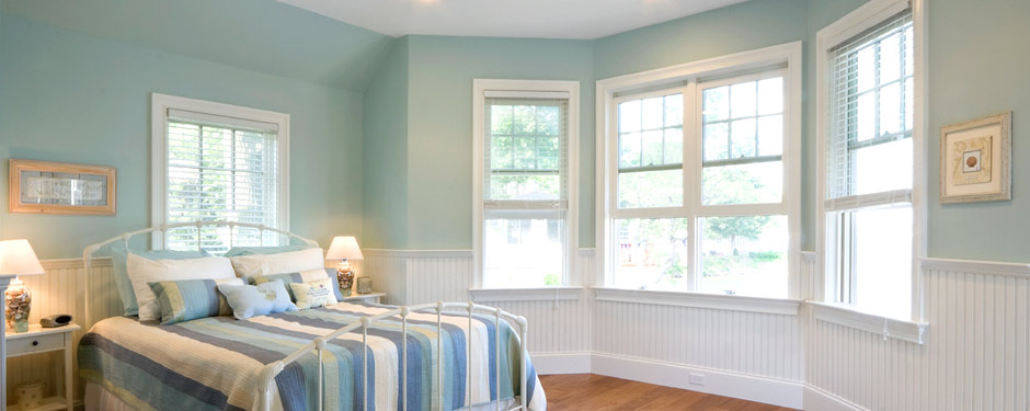 Teal bedroom with large bay windows