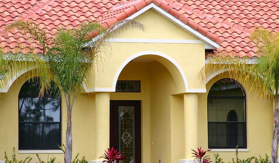 yellow Spanish style home with tile roof